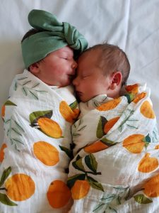 Emma's newborn twins, swaddled in receiving blankets with illustrations of citrus fruit