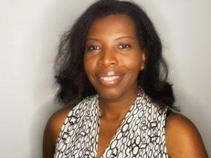 Dr. Meedlen Charles, a Black woman with medium-length wavy dark hair, smiles in a headshot