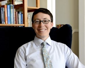 A white-presenting Latinx person with short dark hair and glasses wearing a white collared shirt and tie