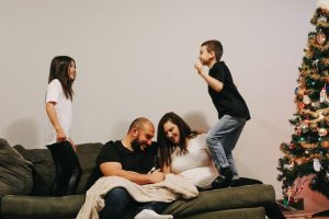 Amy and her partner hold their baby, while their two older children jump on the couch on either side of them