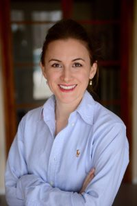 Headshot of Cristen Pascucci, with her hair pulled back, wearing a blue button-down shirt with arms crossed over her chest