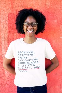 Laurel, a Black femme with short, textured black hair and wearing glasses, stands in front of a red-orange wall and smiles broadly at the camera